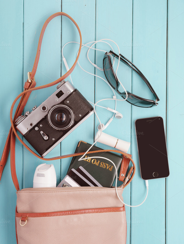 Female bag with a variety of personal belongings and with retro camera.